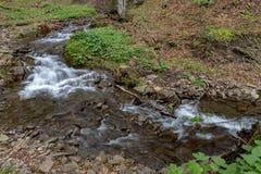 Una corrente veloce in terreno montagnoso Acqua che entra nel fiume indicato in un'esposizione lunga fotografia stock
