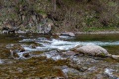 Una corrente veloce in terreno montagnoso Acqua che entra nel fiume indicato in un'esposizione lunga fotografia stock libera da diritti