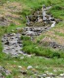 Una corriente pedregosa atraviesa un prado verde con la hierba baja fotos de archivo
