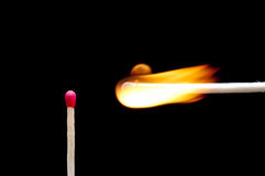 Una corrispondenza burning vicino ad un'altra corrispondenza Fotografia Stock