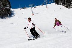 Una corsa con gli sci in discesa dei due sciatori immagini stock libere da diritti