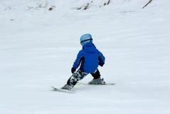 Una corsa con gli sci in discesa del ragazzo Fotografia Stock