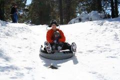 Una corsa della figlia e del papà giù una collina dello Snowy Immagini Stock