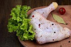 Una coscia di pollo cruda condita sulla tavola prima di predare immagini stock