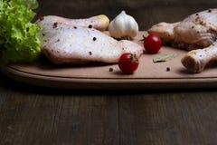 Una coscia di pollo cruda condita sulla tavola prima di predare con il co fotografia stock libera da diritti