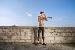 Una costruzione d'allungamento adatta del cielo blu del braccio dell'uomo di forma fisica Fotografia Stock