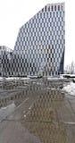 Una costruzione di vetro alta e unicamente a forma di ha situato verticalmente il colpo Immagini Stock