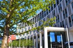 Una costruzione moderna veduta attraverso un albero Immagine Stock Libera da Diritti