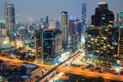 Una costruzione nel settore commerciale a Bangkok alla notte con traffico Immagine Stock