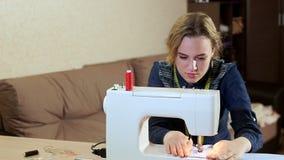 Una costurera joven en casa en la tabla que trabaja con una máquina de coser blanca Ella crea la nueva ropa metrajes
