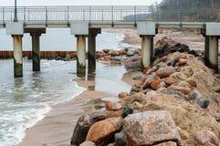 Una cresta dei massi sulla spiaggia, pilastro sul mare immagine stock