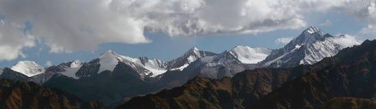 Una cresta delle alte montagne, fotografia panoramica: picchi coperti di neve, ghiacciai che discendono nelle valli, colline nel  Fotografie Stock
