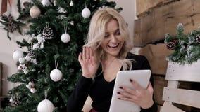 Una criada comunica en Internet en su tableta en una atmósfera de la Navidad metrajes