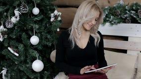 Una criada comunica en Internet en su tableta en una atmósfera de la Navidad almacen de metraje de vídeo