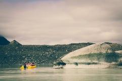 Una crociera gialla del ghiacciaio della barca nel lago Tasman con gli effetti d'annata di colore fotografia stock