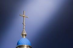 Una cruz cristiana grande en la cual cae un rayo del sol a través de las nubes Foto de archivo