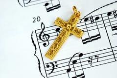 Una cruz de oro en la tapa de una hoja de música Imagenes de archivo