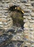 Una cruz del metal en una cerca de piedra imagen de archivo libre de regalías