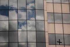 Una cruz reflejada en rascacielos Imagen de archivo libre de regalías