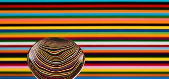 Una cuchara contra un fondo colorido, mostrando la reflexión de fotografía de archivo
