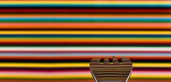 Una cuchara contra un fondo muy colorista, con el fondo foto de archivo