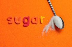 Una cucharilla de azúcar con el azúcar de la palabra Imágenes de archivo libres de regalías