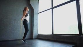 Una cuerda de salto atractiva y atlética de la muchacha, la contratan a ejercicios cardiios almacen de video