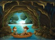 Una cueva con dos niños que montan en un barco de madera Foto de archivo libre de regalías