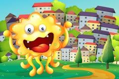 Una cumbre a través de los edificios altos con un monstruo amarillo feliz Fotografía de archivo libre de regalías