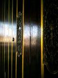 Una decoración de cobre amarillo adornada en puerta de madera marrón oscura imagen de archivo libre de regalías