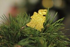 Una decoración de oro del árbol de navidad con las luces Imagen de archivo