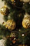 Una decoración de oro del árbol de navidad con las luces Fotografía de archivo