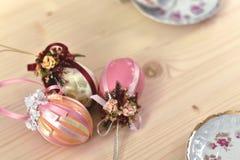 Una decorazione d'annata di Pasqua di tre uova di Pasqua colorate rosa brillanti decorate con i nastri brillanti immagini stock
