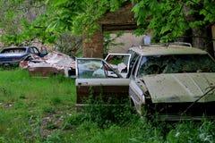 In una delle foreste in Europa le vecchie automobili avariate e dimenticate nell'iarda fotografie stock