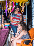 Una dependienta joven teje a otra chica joven en los ornamentos vendidos del pelo apenas por la tarde en la costa en la ciudad de Imágenes de archivo libres de regalías