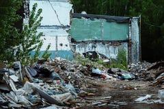 Una descarga de basura y un edificio con las paredes de ladrillo arruinadas en el backgro Fotos de archivo