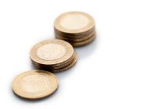 Una diagonal de los tres aisló pilas de monedas Imágenes de archivo libres de regalías