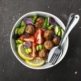 Una dieta sana, equilibrata, sana Polpette, pomodori, riso, cetrioli, fagioli della soia, spinaci, limone, ciotola Vista superior immagine stock