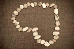 Una dimensión de una variable del corazón de la piedra sobre la madera marrón Imagenes de archivo