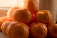 Una disposizione della piramide delle clementine sul davanzale della finestra, con luce solare fotografia stock libera da diritti