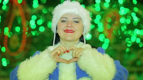 Una doncella sonriente de la nieve muestra un corazón en el árbol de navidad almacen de video