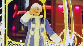 Una doncella sonriente de la nieve que agita un saludo de la ventana que brilla con las luces de un carro almacen de metraje de vídeo