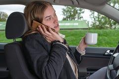 Una donna ? sul telefono e sul caff? bevente mentre conduce l'automobile fotografia stock