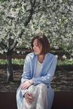 Una donna abbastanza castana dei giovani con i capelli di scarsità in vestiti romantici luminosi ed in un cappotto blu si siede s immagini stock