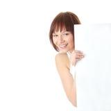Una donna abbastanza giovane che tiene un segno in bianco Immagini Stock Libere da Diritti