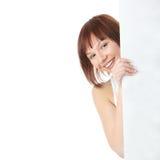 Una donna abbastanza giovane che tiene un segno in bianco Immagini Stock