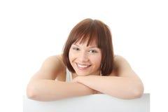 Una donna abbastanza giovane che tiene un segno in bianco Fotografia Stock