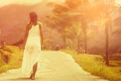 Una donna abbronzata in un vestito bianco cammina in avanti sulla strada La vista dalla parte posteriore Nei precedenti, palme e  fotografia stock