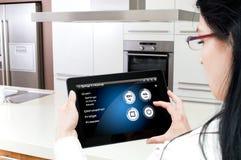 Una donna accende il forno dall'applicazione dello smarthome della compressa Fotografie Stock Libere da Diritti