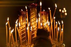 Una donna accende una candela alla chiesa fotografia stock